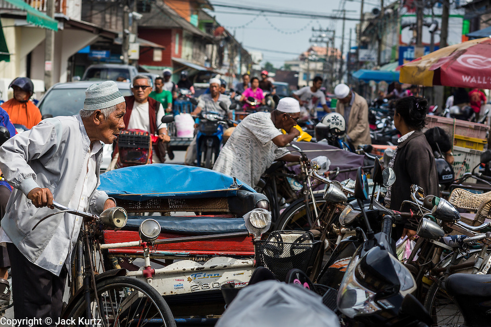 09 JULY 2013 - PATTANI, PATTANI, THAILAND:  A Muslim pedicab driver in traffic in the market in Pattani.  Pattani, along with Narathiwat and Yala, are the only three Muslim majority provinces in Thailand.     PHOTO BY JACK KURTZ