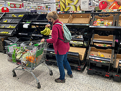 © Licensed to London News Pictures. 22/12/2020. London, UK. A customer in Asda picks up a bunch of bananas as a rush of Christmas shoppers descend on Asda in South West London today causing long queues in the aisles and empty shelves after news of a French travel ban to Europe which has blocked freight from leaving the Port of Dover after a spike of infections due to the Covid-19 mutation. Last week Prime Minister Boris Johnson put London and parts of the South East into Tier 4 lockdown after the new Covid-19 mutation was discovered. Photo credit: Alex Lentati/LNP