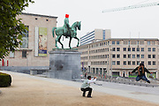 Tourist does a jump while another photographs him on the Kunstberg in the center of Brussels. Statue in Bronze of man on horse is covered by fluo box, for Zinneke parade of a day earlier. Zinneke parade is a yearly theatrical parade made by artists and inhabitants in Brussels working together.