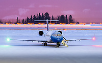 A pre-dawn snow shower, runway sweepers, and lights from the City of Whitehorse come together as Nav Canada's Bombardier CRJ-200ER C-GNVC gets ready for a new day.