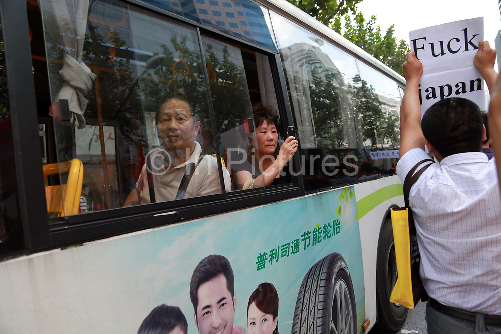 Bystanders watch as protestors display banners and pictures of Chairman Mao while chanting slogans during their march towards the Japanese Consulate in Shanghai, China on 16 September 2012. Torrid protests in several Chinese cities broke out against Japan as it tries to nationalize the disputed Senkaku Islands as it is known in Japan or Diaoyu Island as it is known in China for a second day on Sunday, prompting Japanese Prime Minister Yoshihiko Noda to urge Beijing to protect his country's companies and diplomatic buildings from fresh assaults.