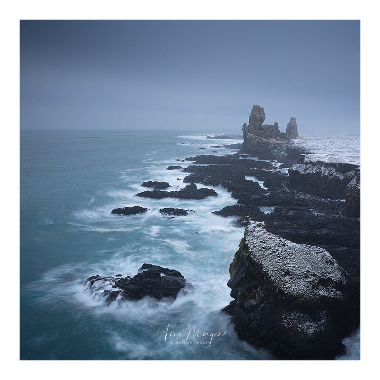 Londrangar basalt rock stacks which are part of an old volcanic crater being pounded by winter Atlantic surf in Snaefellsness Peninsula, Iceland