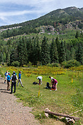 Backpackers prepare to hit the trail after being dropped off by the train. Photograph of the Durango & Silverton Narrow Guage Railroad as it travels between Silverton and Durange, Colorago, USA on a beautiful summer day.