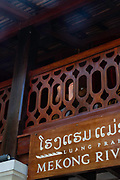 A hotel guests props their feet on a hotel railing; Mekong Riverview Hotel, Luang Prabang, Laos.
