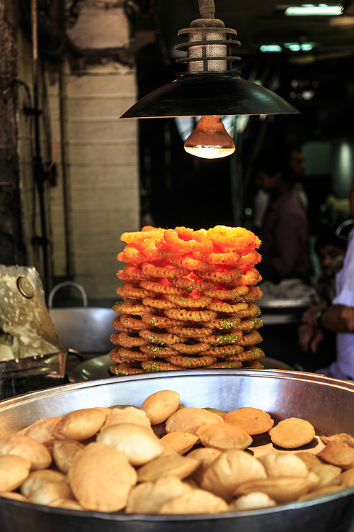 Imarti and kachori for sale in Old Town in New Delhi, India. Imarti or Jhangri is a ring-shaped dessert introduced to India by Mughal cooks. It is made by deep-frying urad flour batter in a kind of circular flower shape, then soaked in sugar syrup. Kachori   is usually a round flattened ball made of fine flour filled with a stuffing of baked mixture of yellow moong dal or Urad Dal.