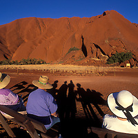 Australia, Northern Territory, Tourists watch setting sun lighting Ayers Rock in Uluru National Park