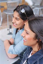 Two teenage girls laughing,