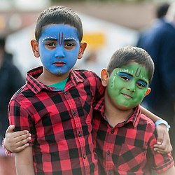 © Licensed to London News Pictures. 05/09/2015. Watford, UK. Brothers, David, aged 5, and Alessandro, aged 4, wear face-paint with gopi dots during their visit to the biggest Janmashtami festival outside of India at the Bhaktivedanta Manor Hare Krishna Temple in Watford, Hertfordshire.  The event celebrates the birth of Lord Krishna and the festival  includes music, dance, food, dramas and more. Photo credit : Stephen Chung/LNP