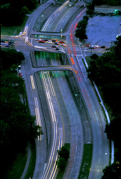 Aerial of traffic driving on parallel streets and an overpass in the Houston area