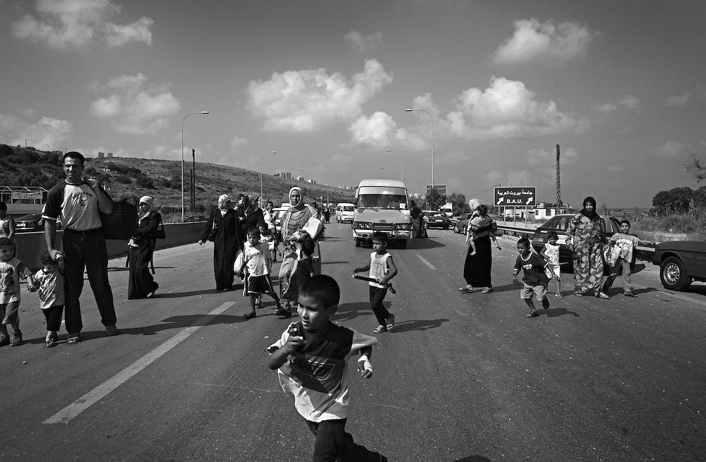 Families from Southern Lebanon cross a bombed-out bridge as they flee Israeli air strikes in the city of Damour, Lebanon, July 13, 2006. <br /> Israeli forces intensified their attacks in Lebanon, with airstrikes that blasted the country's only international airport and the Hezbollah TV station in what was Israel 's heaviest air campaign against Lebanon for 24 years.