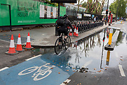 A cyclist rides through collected water on a section of the CS2 cycling superhighway after recent rainfall, on 29th August 2018, in London, England. The CS2 cycle route is about 4.3 miles (6.8 kilometres), from Stratford to Aldgate.