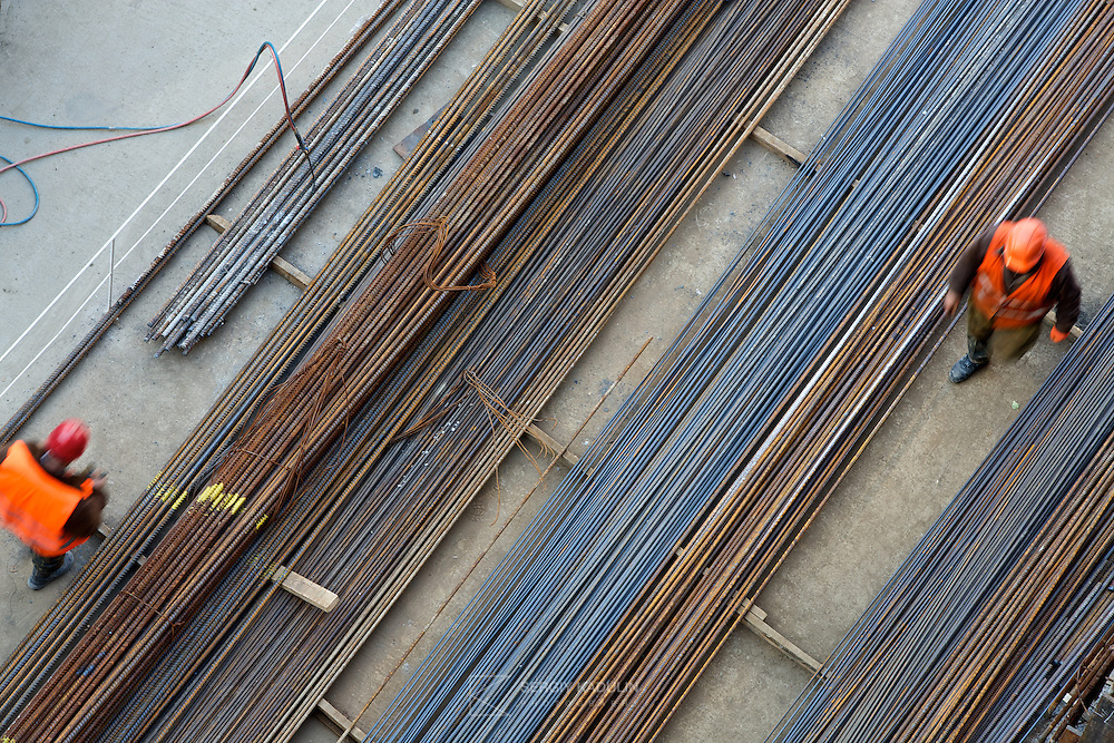 Two workers walking at the construction site of Central Shopping Mall in Kyiv, Ukraine. Top-down view.