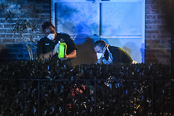 © Licensed to London News Pictures. 18/03/2020. London, UK. Paramedics wipe down equipment and disinfect the area as a patient is removed from a hostel in west London overnight. Paramedics observing new protocols employed when managing patients suspected of coronavirus COVID-19 infection, wear masks, protective aprons and gloves as the pandemic spreads. Members of the public were asked to keep their distance. Photo credit: Guilhem Baker/LNP