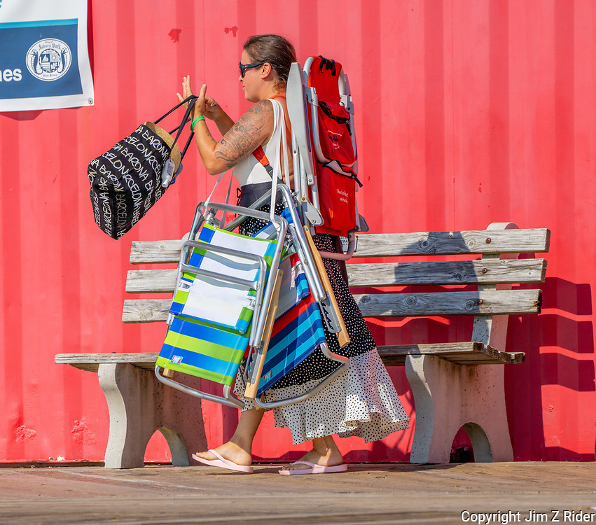 A woman seems to be carrying the entire load for the family as she arrives along the boardwalk. She was near the bathrooms so maybe the kids had other priorities.