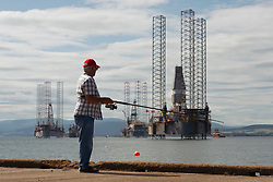 Man fishing on pier with oil and gas platforms  to rear in Cromarty village  on Black Isle on Cromarty Firth, Ross and Cromarty, Scotland, UK