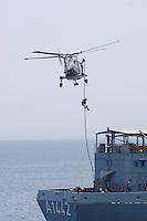 """25 SEP 2006, GOLF VON TADJURA/DJIBOUTI:<br /> Soldaten der Spezialisierten Einsatzkraefte Marine der Fregatte """"Schleswig Holstein"""" mit einem Hubschrauber Typ Sea Lynx fuehren ein """"Fast Roping"""" - das abseilen auf ein fremdes Schiffes zur Ueberpruefung - auf dem Betriebsstoffversorger """"Spessart"""". Die Fregatte ist als Flaggschiff Teil des deutschen Marinekontingents der OPERATION ENDURING FREEDOM und operiert im Seegebiet am Horn von Afrika<br /> IMAGE: 20060925-01-133<br /> KEYWORDS: Dschibuti, Bundeswehr, Marine, Soldat, Soldaten, Helikopter, helicoter"""