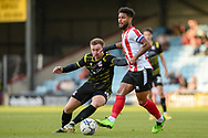 Liam Bridcutt (23) of Lincoln City and Scunthorpe United Jordan Hallam (10) battles for possession during the Pre-Season Friendly match between Scunthorpe United and Lincoln City at the Sands Venue Stadium, Scunthorpe, England on 27 July 2021.