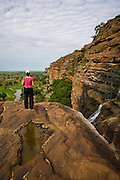 Tourist looking at the landscape on the ascent from Kani-Kombolé to Djiguibombo village. Waterfalls formed during the rainy season drop from the Bandiagara Escarpment cliff permitting tourists to cool off from the hiking. The Dogon Country is the most visited part of Mali with tourists visiting its tipical  villages that can be located on the cliff, on the sandy plain or in the rocky plateau