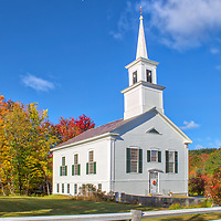 New England fall foliage framing the white steeple historic Fitzwilliam Community Church in Fitzwilliam , NH. <br />