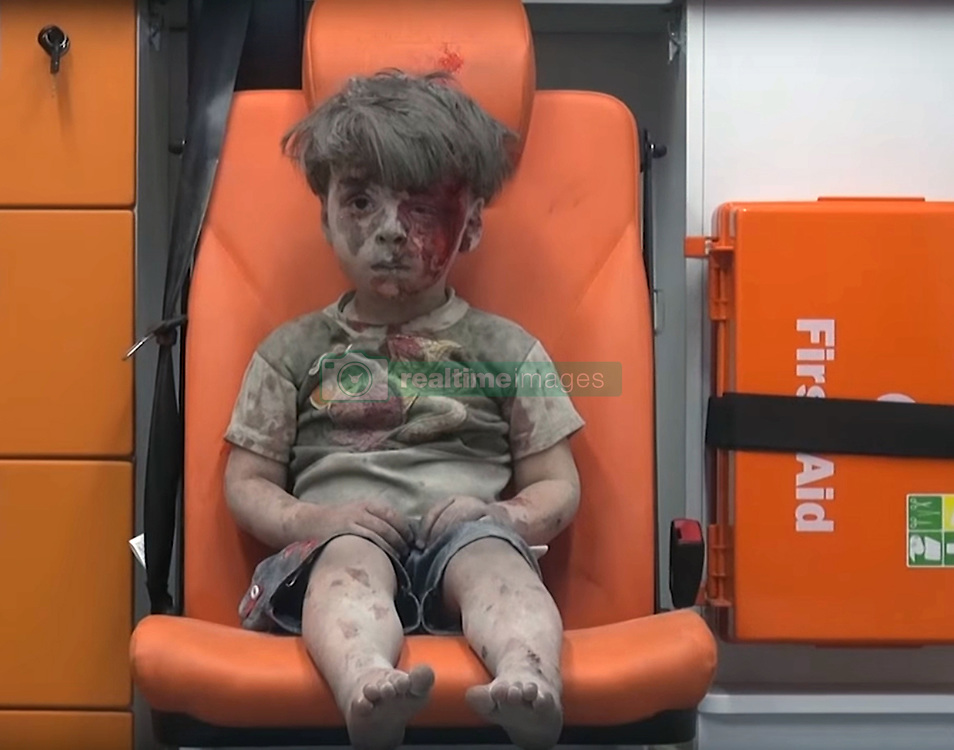 August 17, 2016 - Aleppo, Syria - HOMELESS: Five-year-old wounded Syrian boy OMRAN DAQNEESH sits alone and silent, with a bloodied face sitting in the back of an ambulance after he sustained injuries during an airstrike. Daqneesh was injured, in an alleged Russian Air Force strike on the rebel-held al-Qaterji neighborhood of Aleppo. Omran suffered a wound to his head and was taken to a hospital known as M10 and later discharged. Daqneesh was rescued with his parents and three siblings, then aged one, six, and ten. His 10-year-old brother, Ali, died on August 20, 2016, of his injuries. The apartment building collapsed shortly after the family was rescued. Eight people died in the air strike, including five children. Caked in dust, Omran is one of the thousands of Syrian children caught in an endless war. Aleppo, the northern Syrian city, for years has been a battleground between government and opposition forces in this endless Civil War. The eastern section, where civilians live in dire conditions, has been shredded by barrel bombs and airstrikes. Omran Daqneesh, silent and in shock in the back of an ambulance, the left side of his face is smeared with blood. He doesn't make a sound. (Credit: © Mahmoud Rslan/Aleppo Media Center via ZUMA Wire)
