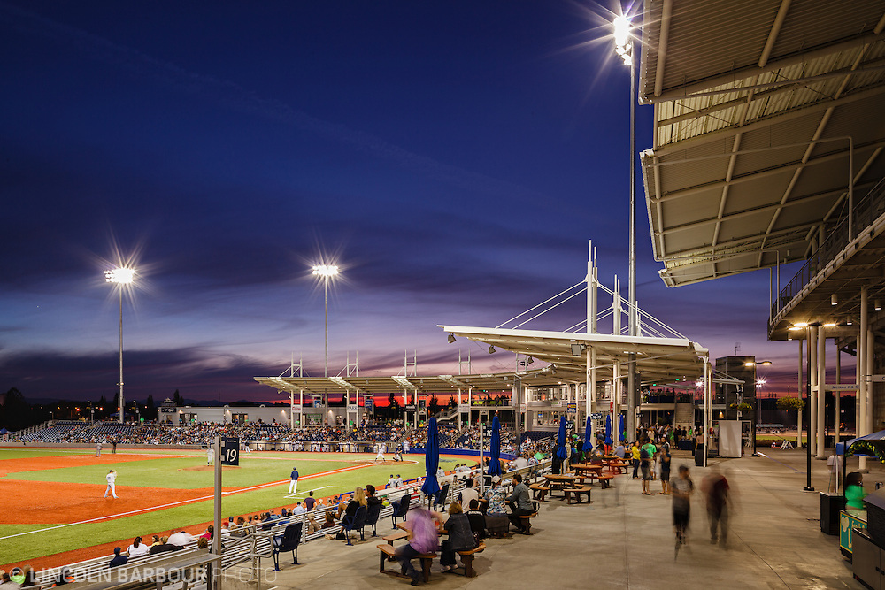 As evening sets in, a minor league baseball game is in play as seen from along the third baseline towards the outfield showing the stands and fans.  The sky is quite dramatic overhead turning to a deep blue with a hint of neon pink off in the distance.