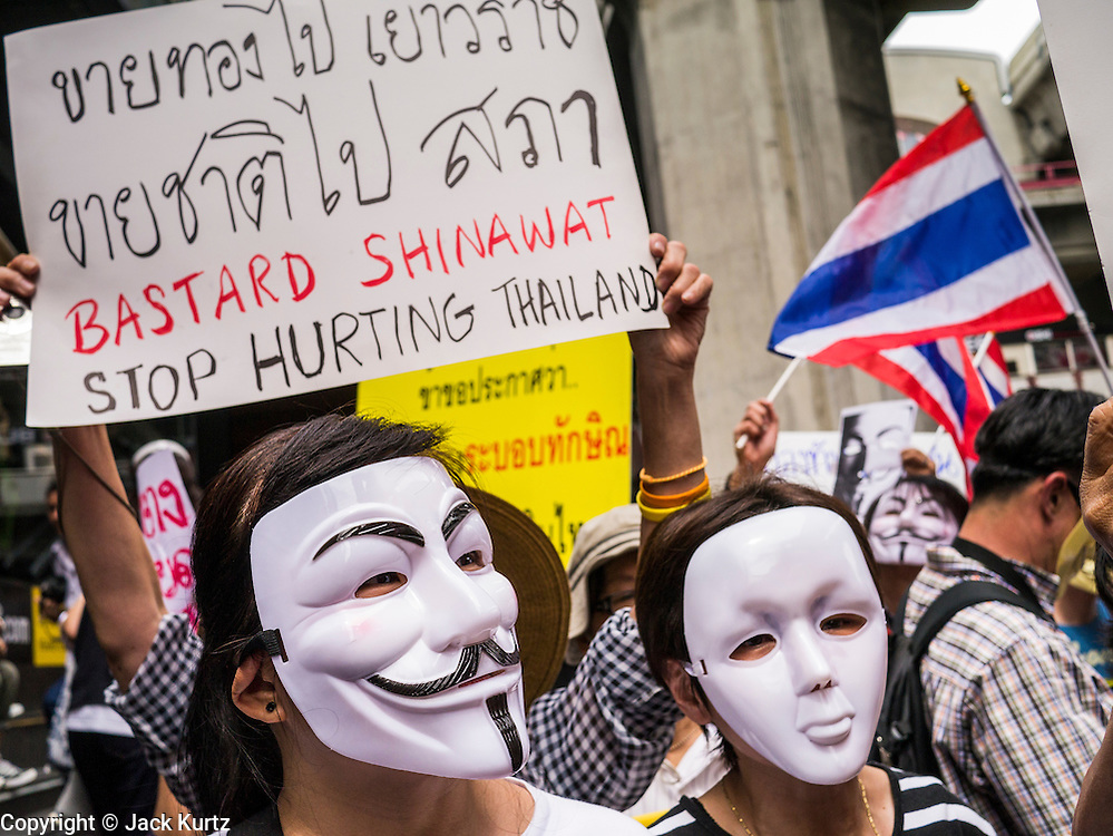"""02 JUNE 2013 - BANGKOK, THAILAND:   An anti-government protesters wearing Guy Fawkes masks march through the skywalk system in Bangkok. About 300 people wearing the Guy Fawkes mask popularized by the movie """"V for Vendetta"""" and Anonymous, the hackers' group, marched through central Bangkok Sunday demanding the resignation of Prime Minister Yingluck Shinawatra. They claim that Yingluck is acting as a puppet for her brother, former Prime Minister Thaksin Shinawatra, who was deposed by a military coup in 2006 and now lives in exile in Dubai.   PHOTO BY JACK KURTZ"""