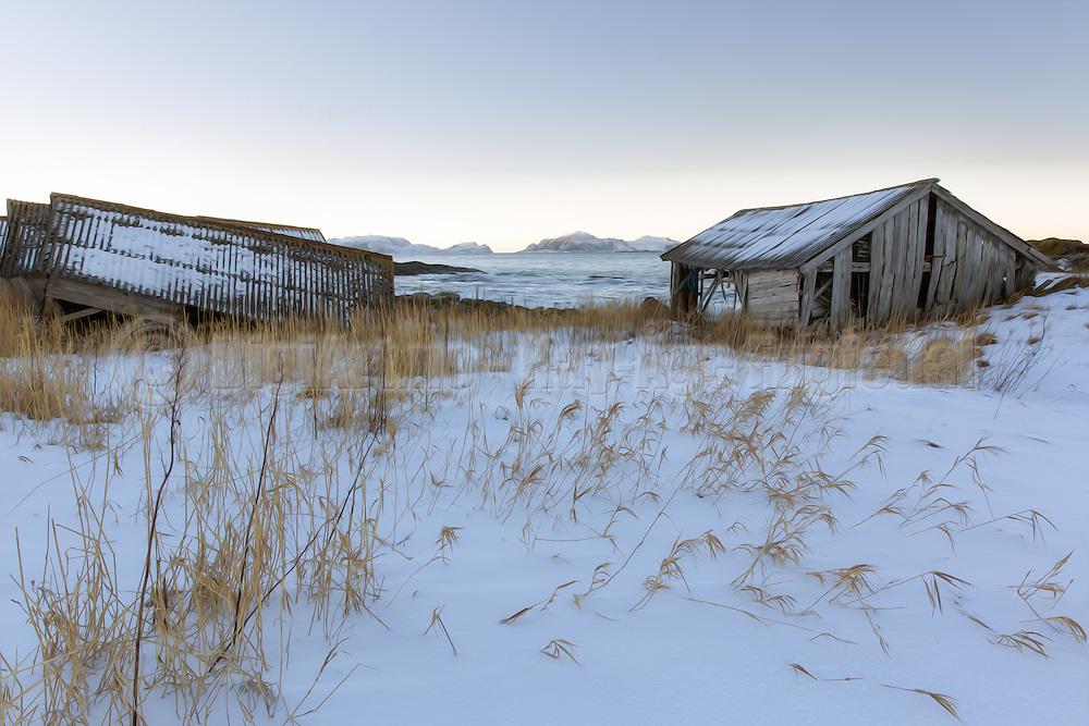 Old bouthouses by the sea in snow landscape. View to Nerlandsøy, Norway   Gamle naust ved sjøen i snølandskap. Utsikt mot Nerlandsøya.
