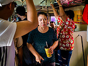 11 APRIL 2018 - BANGKOK, THAILAND:  A woman looks for a seat on a packed train to Ayutthaya on the first day of the Songkran travel period. Songkran is the traditional Thai New Year and is one of the busiest travel periods of the year as Thais leave the capital and go back to their home provinces or resorts in tourist areas. Trains and busses are typically jammed the day before the three day Songkran holiday starts. The government has extended the official holiday period through Monday, 16 April because one day of the Songkran holiday fell on the weekend, giving many workers a five day holiday.     PHOTO BY JACK KURTZ
