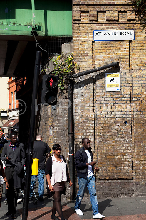 Street scene on Brixton Road, a multicultural area in South London. This is on the corner of Atlantic Road underneath the railway bridge. Brixton is a district in south London, England, in the London Borough of Lambeth. The area is identified in the London Plan as one of 35 major centres in Greater London. Brixton is predominantly residential with a prominent street market and substantial retail sector. It is a multiethnic community, with around 24 percent of Brixton's population being of African and Caribbean descent, giving rise to Brixton as the unofficial capital of the British African-Caribbean community.