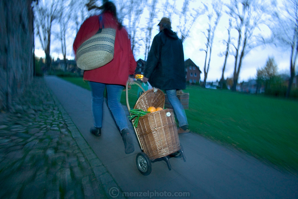(MODEL RELEASED IMAGE). An hour after they arrived at the Saturday market in Ahrensburg (a neighboring town to their home in Bargteheide), the Melanders walk home with their produce, cutting through the town square, past a 19th century church. Hungry Planet: What the World Eats (p. 137).