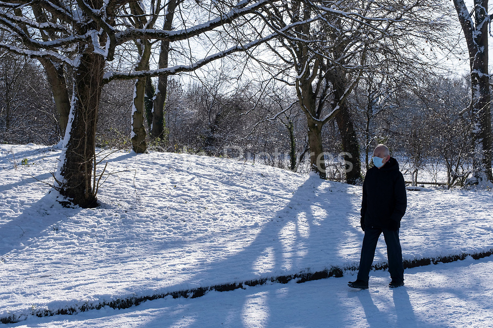 Man wearing a face mask due to the coronavirus pandemic in the snow in Canon Hill Park in Moor Green on 25th January 2021 in Birmingham, United Kingdom. Deep snow arrived in the Midlands giving some light relief and fun during the current lockdown for people who simply enjoyed the weather.