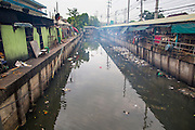 "03 OCTOBER 2012 - BANGKOK, THAILAND:  Khlong Toey runs along Khlong Toey Market in Bangkok. Khlong is the Thai word for canal. This canal used to go all the way to the old imperial center of Bangkok but has been filled in now. This stretch of the canal is used for waste water from the market. Khlong Toey (also called Khlong Toei) Market is one of the largest ""wet markets"" in Thailand. Thousands of people shop in the sprawling market for fresh fruits and vegetables as well meat, fish and poultry every day.       PHOTO BY JACK KURTZ"