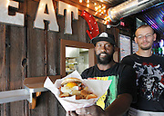 """Ortarius """"Spanky"""" Williams (left) is the chef at the Kaskaskia River House, and is assisted by cook Jason Conaway. Here, """"Spanky"""" holds up an Eggsquisite Burger -- an over-easy egg on a bun topped with onion straws and bacon bits, plus a side of home-made potato chips."""