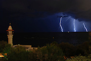 Israel, Mediterranean sea, Lightning storm. El Bahar Mosque in the foreground