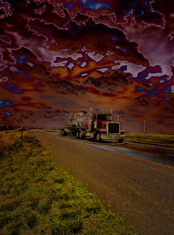 A Sinister 18 Wheeler travels down a forbidding road at a dark midnight hour through ominous skies.