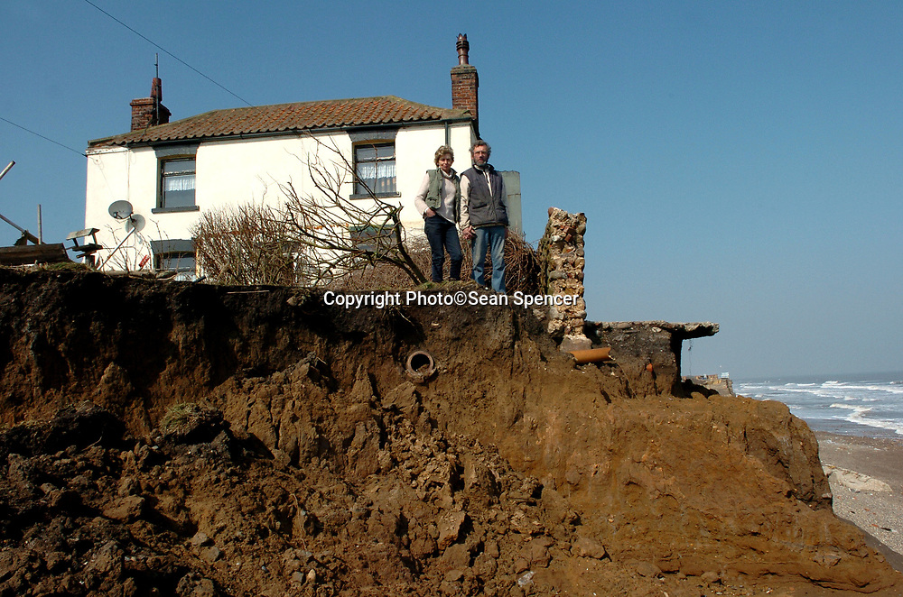 26 March 2007: Colin and Josephine Arnold today outside their home in Ulrome, East Yorkshire, which is perched precariously on a cliff top after recent high tides and bad weather. The couple have lost over 70 feet of land in the 19 years they have lived there. Last week they lost another five foot. The couple have asked Ian Pearson, the Minister for Climate Change, to visit them. At the moment, residents do not receive compensation when they lose their property to erosion. The Arnold's claim that nearby sea defences have installed in 1992 have made things worse for them.<br /> see story<br /> Picture:Sean Spencer/Hull News & Pictures 01482 210267/07976 433960<br /> High resolution picture library at http://www.hullnews.co.uk<br /> ©Sean Spencer/Hull News & Pictures Ltd