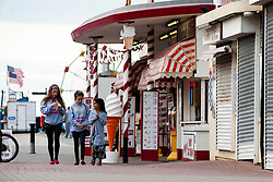 Three girls walk past MacDonalds Ices a Traditional British seaside fast food stall on the sea front at Cleethorpes Lincolnshire..1 July 2012.Image © Paul David Drabble