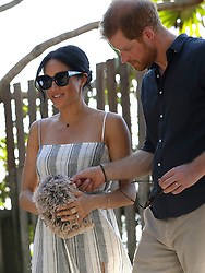 The Duchess of Sussex holds a gift from a member of the public as she walks along Kingfisher Bay Jetty with the Duke of Sussex during a visit to Fraser Island, Queenland, on day seven of the Duke and Duchess of Sussex's visit to Australia.