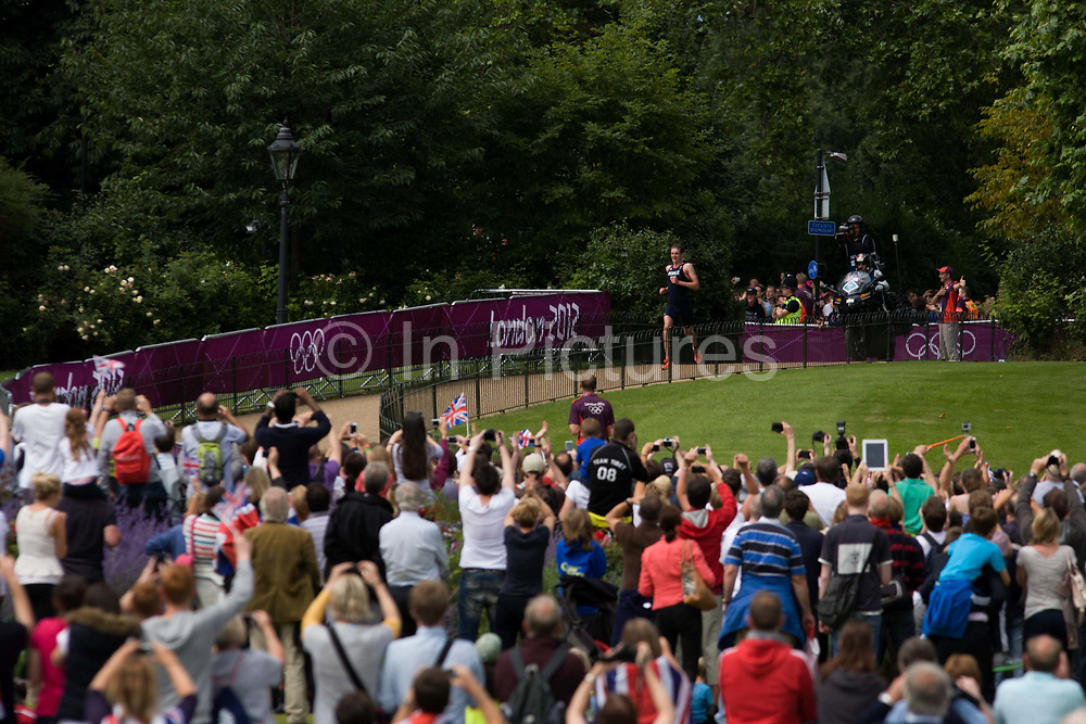 Cheered on by an ecstatic home crowd, Team GB triathlete Jonathan Brownlee runs through London's Hyde Park for the Mens' Triathlon competition in Hyde Park for his Bronze medal place during the London 2012 Olympics, the 30th Olympiad. The Triathlon competitors raced over a 1.5km swim, a 43km bike race and a 10km run - eventually won by Team GB's Alistair Brownlee, Spain's Javier Gomez and Jonathan Brownlee (brother of the winner). The venue was the Hyde Park 142 hectares (350 acres)[ Hyde Park in the heart of the capital, one of the largest parks in central London and the site of the Victorian Great Exhibition of 1851.