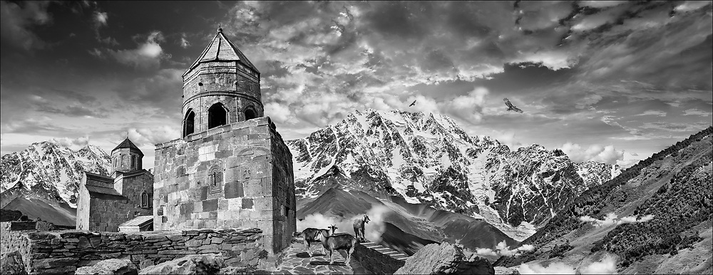Sacred Stone - Black and white photo art print of Gergeti Holy Trinity (Tsminda Sameba) Georgian Orthodox and Apostolic Church, 14th century, Gergeti, Khevi province, Georgia (country) by Paul Williams.<br /> <br /> Gergeti Holy Trinity Church is one of the most remote churches in the world. It is a slow climb up to  remote town of Gergeti in northern Georgia situated at 1,740 m (5,710 ft) above sea level. From Stephantsminda it is a steep climb for 1 1/2 hours to the church of Gergeti Holy Trinity, although a new road will make access for mass tourism easy in 2019. .<br /> <br /> Visit our LANDSCAPE PHOTO ART PRINT COLLECTIONS for more wall art photos to browse https://funkystock.photoshelter.com/gallery-collection/Places-Landscape-Photo-art-Prints-by-Photographer-Paul-Williams/C00001WetsxVxNTo