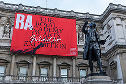© Licensed to London News Pictures. 28/09/2020. LONDON, UK. The masked Joshua Reynolds statue in front of a sign for the Summer Exhibition at the Royal Academy of Arts in Piccadilly which, due to the Covid-19 lockdown, is taking place for the first time in the autumn.  Over 1000 works in a range of media by Royal Academicians, established and emerging artists, feature in the exhibition which runs from 6 October 2020 – 3 January 2021.  Photo credit: Stephen Chung/LNP