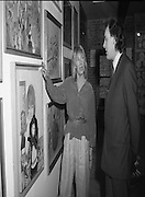 """Pauline Bewick Art Exhibition..1986..03.06.1986..06.03.1986..3rd June 1986..At the Guinness Hop Store,Dublin,artist Pauline Bewick is having an exhibition of her work.The exhibition called """"2 to 50 years""""is a display of her work from age 2 to the present.the art work ranges from simple pencil sketches to more complex paintings and lino cuts...Image shows the artist,Pauline Bewick,discussing her work """"Holly and Ell Coffey Doll"""" with Mr John Taylor,Director,Taylor Galleries."""