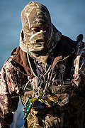 Tony Troxell wades back to shore after resetting decoys while duck hunting in Shamrock, Oklahoma