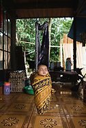 Loklahung, Indonesia - February 28, 2017: Five-month-old Regina naps on the family's porch in a village in Loklahung, South Kalimantan, located on the island of Borneo.