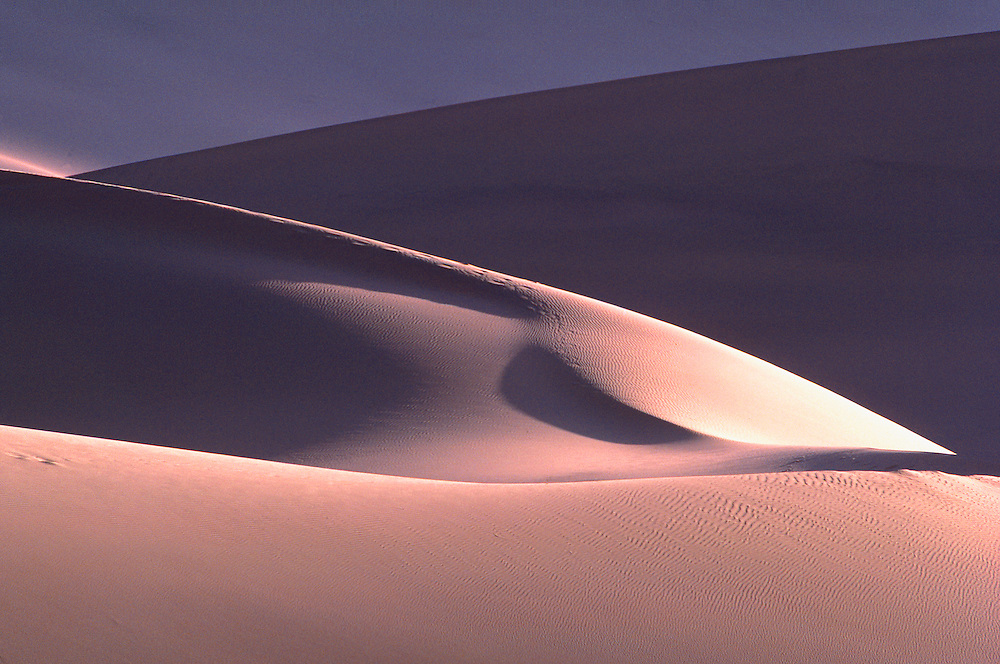 Late light forms shadows among the sand dunes at Dunhuang, China.