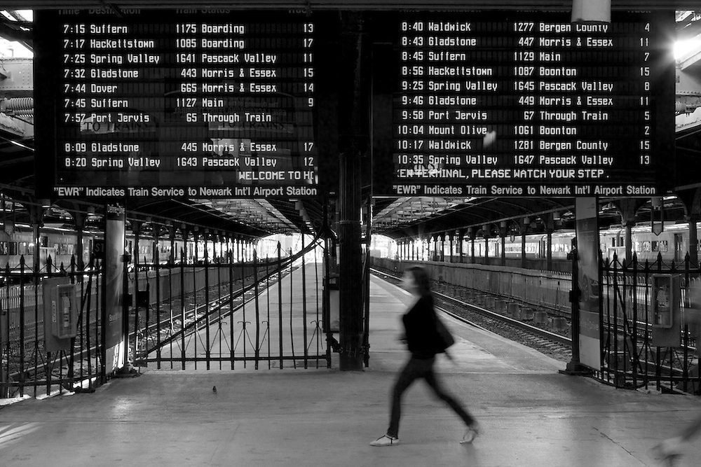 Rushing to make her train, a hurried commuter passes the track assignment board.