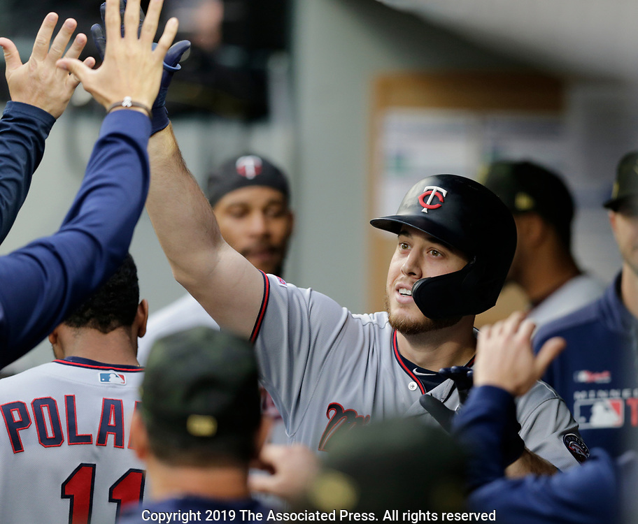 Minnesota Twins' C.J. Cron celebrates in the dugout after hitting a solo home run against the Seattle Mariners during the second inning of a baseball game, Saturday, May 18, 2019, in Seattle. (AP Photo/John Froschauer)