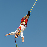 In brightly colored traditional costumes, performers recreating a traditional Mayan ceremony of swinging from a tall pole suspended only by ropes at Xcarat Maya theme park south of Cancun and Playa del Carmen on Mexico's Yucatana Peninsula.