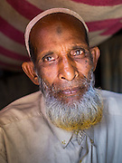 07 NOVEMBER 2014 - SITTWE, RAKHINE, MYANMAR: A Rohingya Muslim man in his tent in an IDP camp for Rohingya. After sectarian violence devastated Rohingya communities and left hundreds of Rohingya dead in 2012, the government of Myanmar forced more than 140,000 Rohingya Muslims who used to live in and around Sittwe, Myanmar, into squalid Internal Displaced Persons camps. The government says the Rohingya are not Burmese citizens, that they are illegal immigrants from Bangladesh. The Bangladesh government says the Rohingya are Burmese and the Rohingya insist that they have lived in Burma for generations. The camps are about 20 minutes from Sittwe but the Rohingya who live in the camps are not allowed to leave without government permission. They are not allowed to work outside the camps, they are not allowed to go to Sittwe to use the hospital, go to school or do business. The camps have no electricity. Water is delivered through community wells. There are small schools funded by NOGs in the camps and a few private clinics but medical care is costly and not reliable.   PHOTO BY JACK KURTZ
