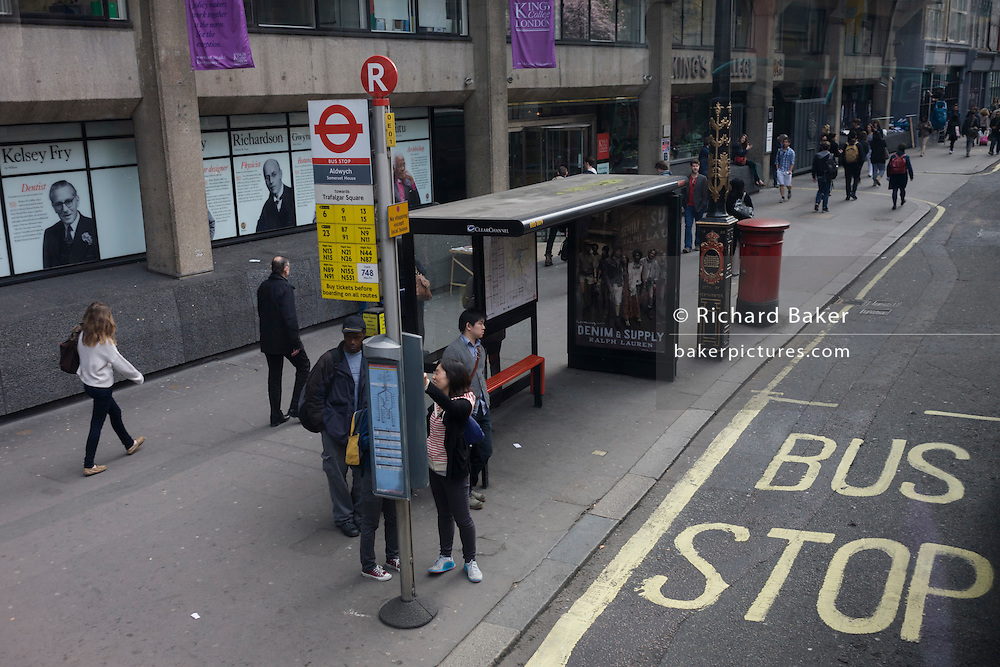 Aerial view of pedestrians and a city bus stop outside King's College on the Strand.